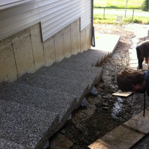 Exposed aggregate walkway with many steps on side of home