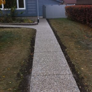 Exposed aggregate walkway from front of home to the back