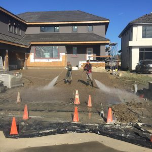 Workers cleaning an exposed aggregate driveway
